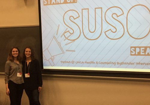 Two students standing in front of a presentation for Stand Up Speak Out